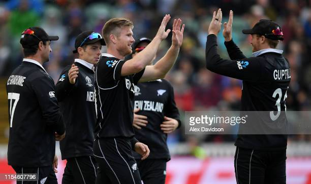 Jimmy Neesham of New Zealand celebrates taking the wicket of Najibullah Zadran of Afghanistan with his teammates during the Group Stage match of the...