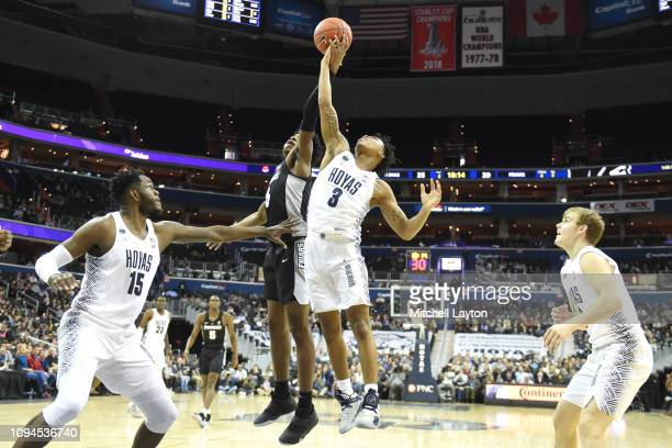 Jimmy Nichols Jr #5 of the Providence Friars and James Akinjo of the Georgetown Hoyas fight for a loose ball during a college basketball game at the...