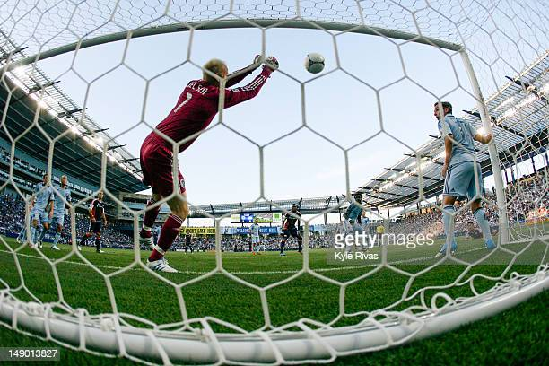 Jimmy Nielsen of the Sporting KC knocks away a header from Ryan Guy of the New England Revolution early in the first half at Livestrong Sporting Park...
