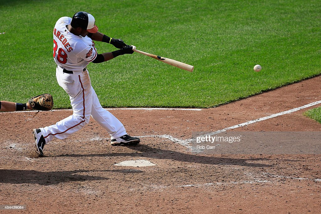 Jimmy Paredes #38 of the Baltimore Orioles connects for a two RBI single against the Minnesota Twins in the seventh inning of the Orioles 12-8 win at Oriole Park at Camden Yards on August 31, 2014 in Baltimore, Maryland.