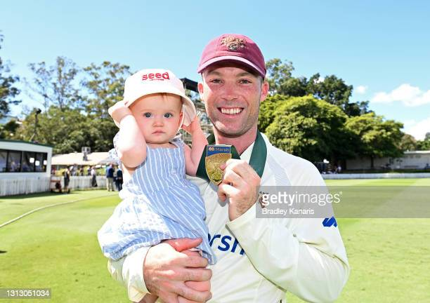 Jimmy Peirson of Queensland celebrates victory with daughter Evie during day four of the Sheffield Shield Final match between Queensland and New...