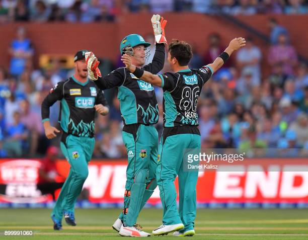 Jimmy Pierson of the Brisbane Heat celebrates with Yasir Shah of the Brisbane Heat after taking the wicked of Travis Head of the Adelaide Strikers...