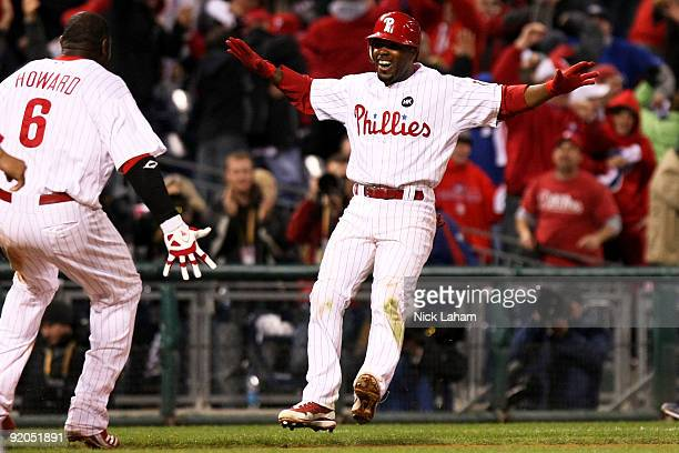 Jimmy Rollins and Ryan Howard of the Philadelphia Phillies celebrate after Rollins hit a game-winning 2-run double in the bottom of the ninth inning...