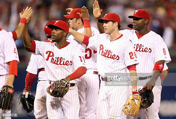 Jimmy Rollins, Chase Utley and Ryan Howard of the Philadelphia Phillies celebrate with their teammates after their 3-2 win against the Los Angeles...