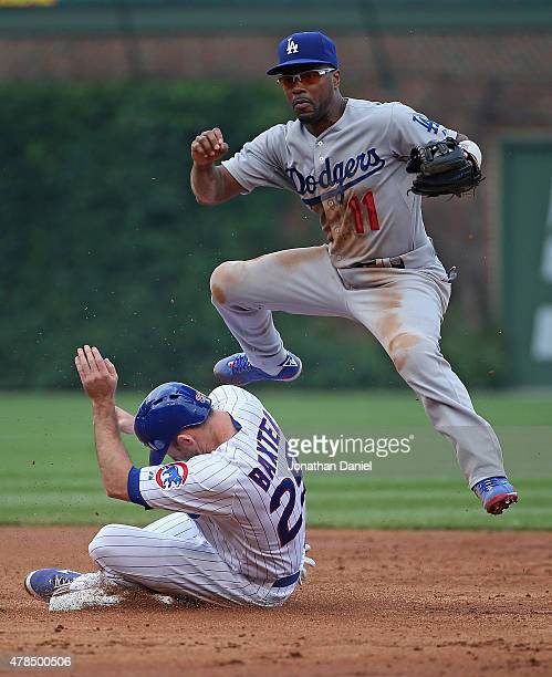 Jimmy Rollins of the Los Angeles Dodgers jumps over Mike Baxter of the Chicago Cubs before turning a double play in the 2nd inning at Wrigley Field...