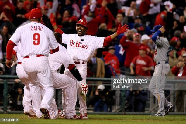 Jimmy Rollins of the Philadelphia Phillies celebrates with teammates after Rollins hit a gamewinning 2run double in the bottom of the ninth inning to...