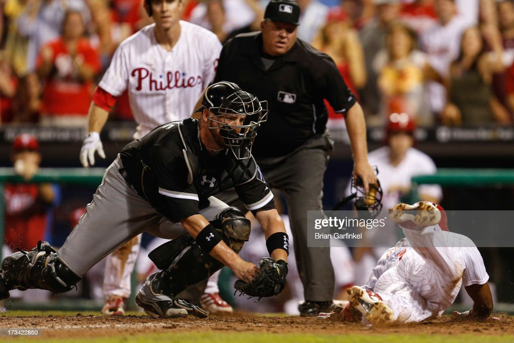 Jimmy Rollins #11 of the Philadelphia Phillies dives home avoiding the tag by Tyler Flowers #21 of the Chicago White Sox to win the game in the thirteenth inning of the second game of a double header at Citizens Bank Park on July 14, 2013 in Philadelphia, Pennsylvania. The Phillies won 2-1 in the thirteenth inning.