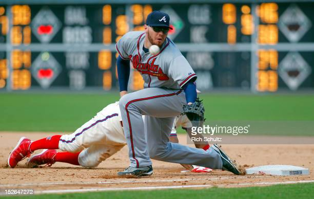 Jimmy Rollins of the Philadelphia Phillies dives into first base on a pick off attempt as the ball gets by first baseman Freddie Freeman of the...