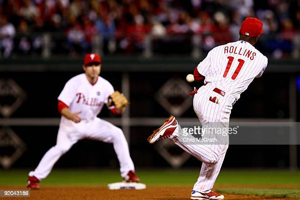 Jimmy Rollins of the Philadelphia Phillies flips the ball to Chase Utley to force out James Loney of the Los Angeles Dodgers on a fielder's choice...