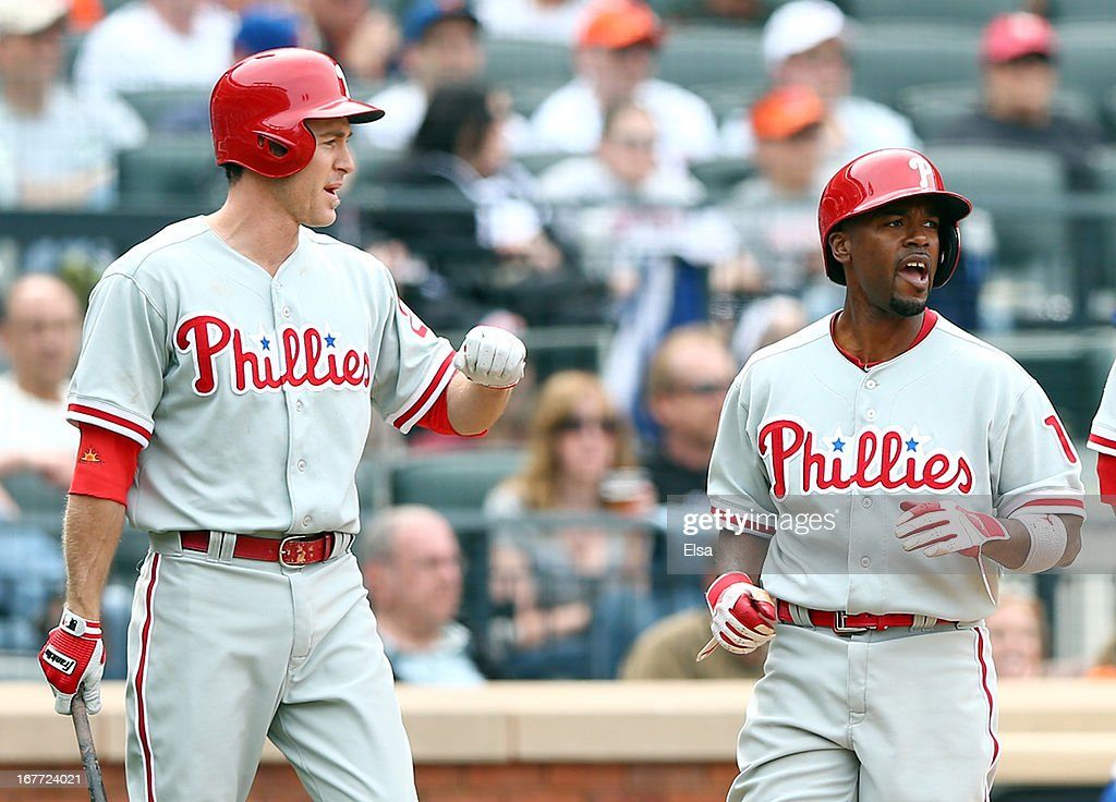 Jimmy Rollins #11 of the Philadelphia Phillies is congratulated by teammate Chase Utley #26 after Rollins scored on an hit by Ryan Howard in the seventh inning against the New York Mets on April 28, 2013 at Citi Field in the Flushing neighborhood of the Queens borough of New York City.