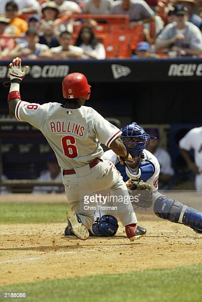 Jimmy Rollins of the Philadelphia Phillies is tagged out at home plate by Jason Phillips of the New York Mets to end the top of the sixth inning on...