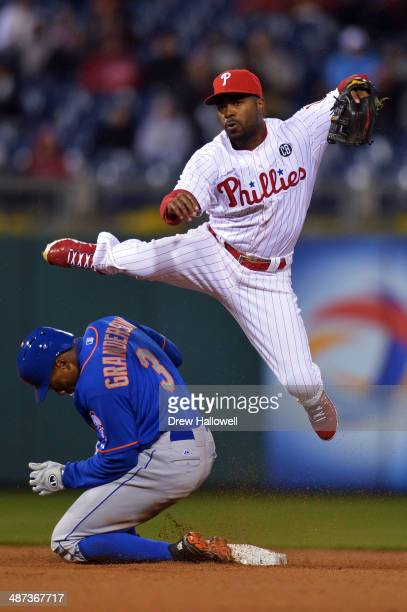 Jimmy Rollins of the Philadelphia Phillies jumps after forcing out Curtis Granderson of the New York Mets on a double play in the second inning at...