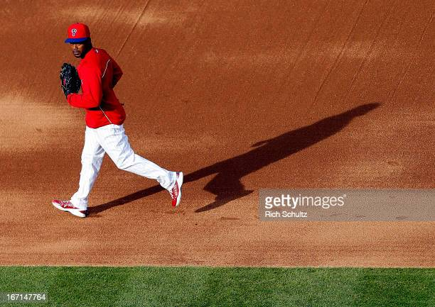 Jimmy Rollins of the Philadelphia Phillies runs the basses with his glove for protection during batting practice before a game against the St Louis...