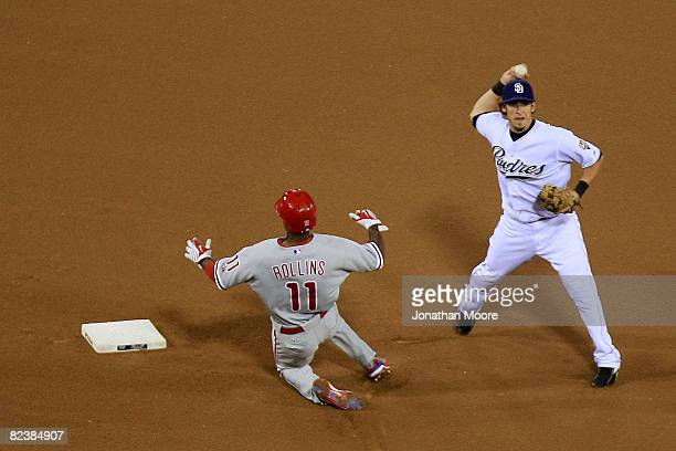 Jimmy Rollins of the Philadelphia Phillies slides in to second base as Sean Kazmar of the San Diego Padres throws to first for the double play during...