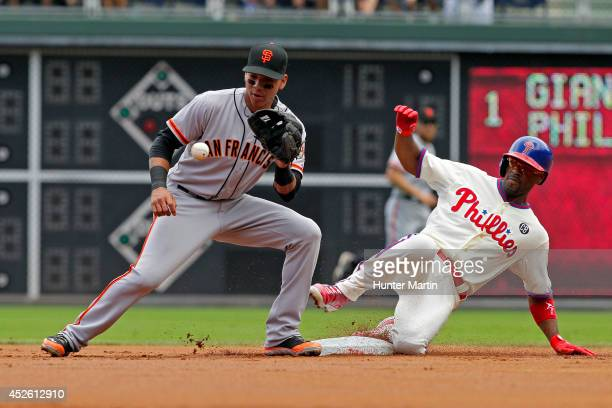 Jimmy Rollins of the Philadelphia Phillies slides into second base with a double in the first inning as Ehire Adrianza of the San Francisco Giants...