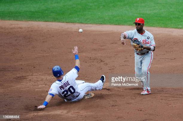 Jimmy Rollins of the Philadelphia Phillies turns a double play as Jason Pridie of the New York Mets slides to second base in the third inning during...