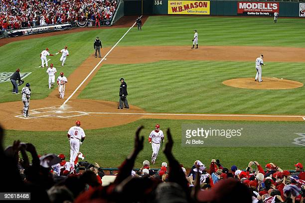 Jimmy Rollins Shane Victorino and Chase Utley of the Philadelphia Phillies all run towards home plate as they scored on a 3run home run in the bottom...
