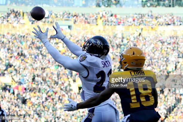 Jimmy Smith of the Baltimore Ravens makes an interception in front of Randall Cobb of the Green Bay Packers in the first quarter at Lambeau Field on...