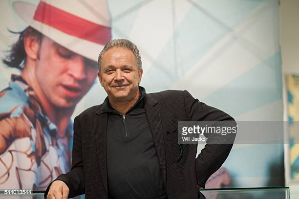 Jimmy Vaughan poses in front of a photo of his brother Stevie Ray at GRAMMY Museum Mississippi on June 29 2016 in Cleveland Mississippi
