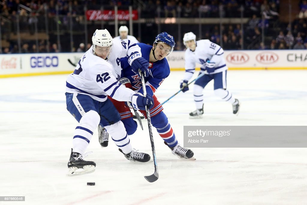 Jimmy Vesey #26 of the New York Rangers and Tyler Bozak #42 of the Toronto Maple Leafs fight for the puck in the third period during their game at Madison Square Garden on December 23, 2017 in New York City.
