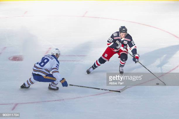 Jimmy Vesey of the New York Rangers carries the puck in the offensive zone with Zemgus Girgensons of the Buffalo Sabres defending during the first...