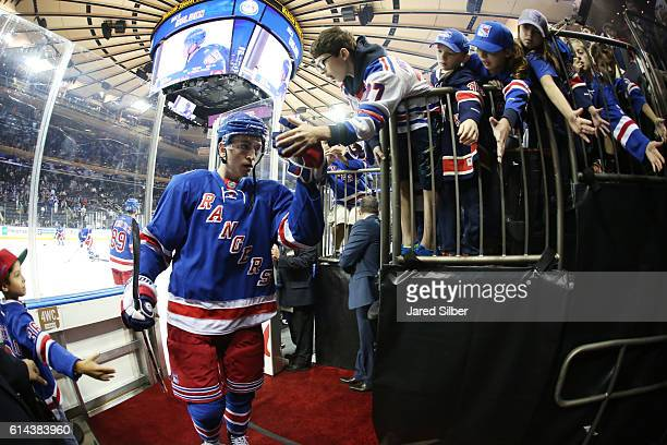 Jimmy Vesey of the New York Rangers highfives fans during pregame warmups before the game against the New York Islanders at Madison Square Garden on...