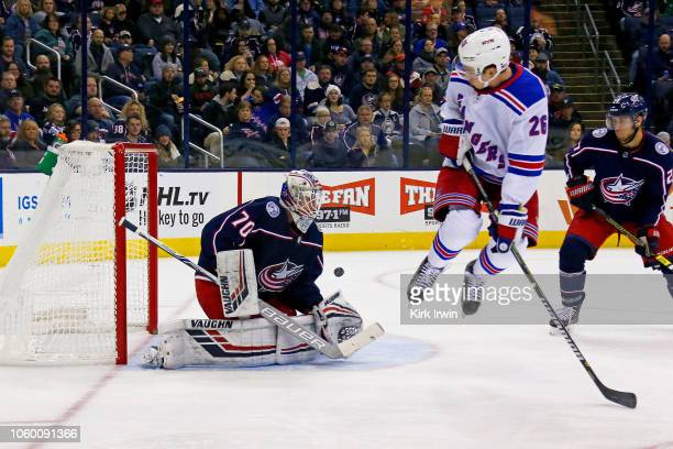Jimmy Vesey of the New York Rangers jumps out of the way of the puck while screening Joonas Korpisalo of the Columbus Blue Jackets during the first...