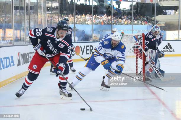 Jimmy Vesey of the New York Rangers plays the puck against Benoit Pouliot of the Buffalo Sabres during the 2018 Bridgestone NHL Winter Classic at...