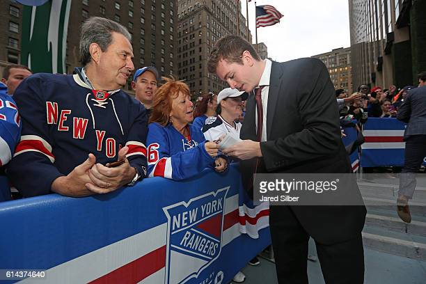 Jimmy Vesey of the New York Rangers signs autographs for fans as he walks down the Blue Carpet prior to the game against the New York Islanders at...