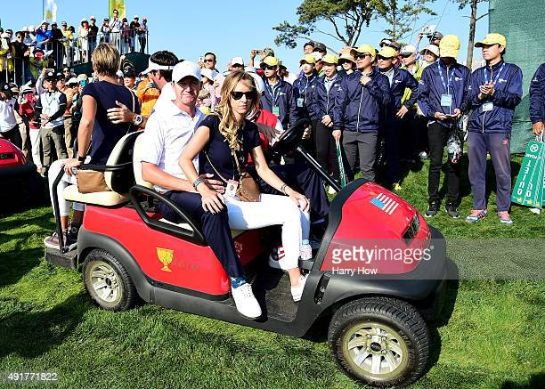 Jimmy Walker and Bubba Watson of the United States Team wait on a golf cart with their wives during the Thursday foursomes matches at The Presidents...