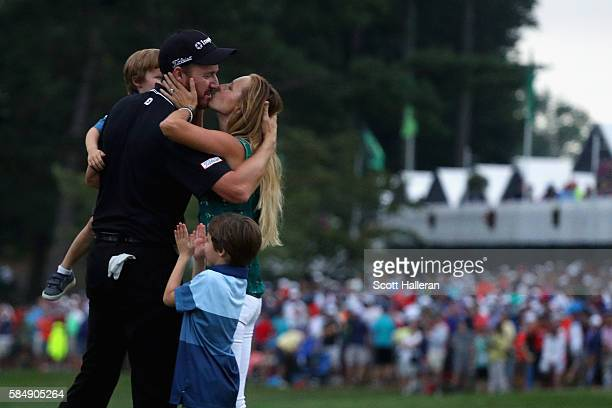 Jimmy Walker of the United States celebrates with his wife Erin and sons Beckett and Mclain after making par on the 18th hole to win the 2016 PGA...