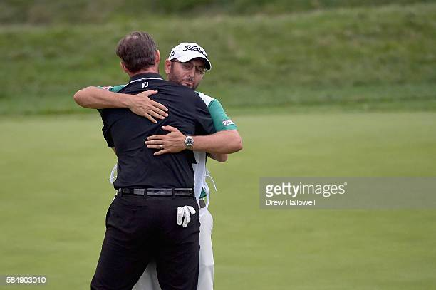 Jimmy Walker of the United States hugs caddie Andy Sanders after his putt for par on the 18th hole to win the 2016 PGA Championship at Baltusrol Golf...
