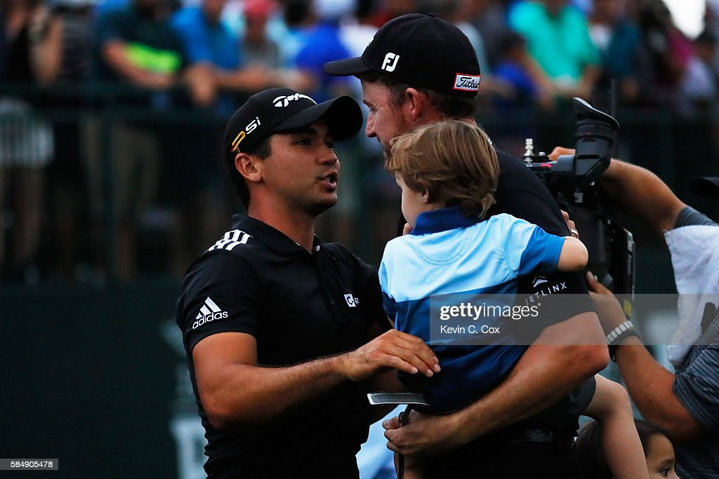 Jimmy Walker (C) of the United States is congratulated on his victory by Jason Day (L) of Australia while holding his son Beckett (R) on the 18th green during final round of the 2016 PGA Championship at Baltusrol Golf Club on July 31, 2016 in Springfield, New Jersey.