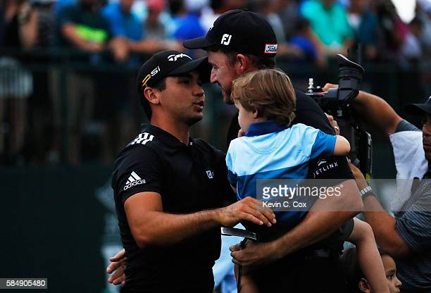 Jimmy Walker of the United States is congratulated on his victory by Jason Day of Australia while holding his son Beckett on the 18th green during...