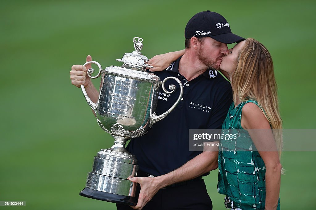 Jimmy Walker (L) of the United States kisses his wife Erin (R) while holding with the Wanamaker Trophy in celebration of his victory during the 2016 PGA Championship at Baltusrol Golf Club on July 31, 2016 in Springfield, New Jersey.
