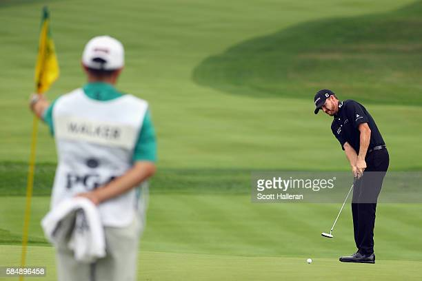 Jimmy Walker of the United States putts for birdie on the third hole as caddie Andy Sanders holds the flag during the final round of the 2016 PGA...