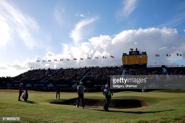 Jimmy Walker of the United States putts on the 18th green as Hideto Tanihara of Japan looks on during the first round of the 146th Open Championship...
