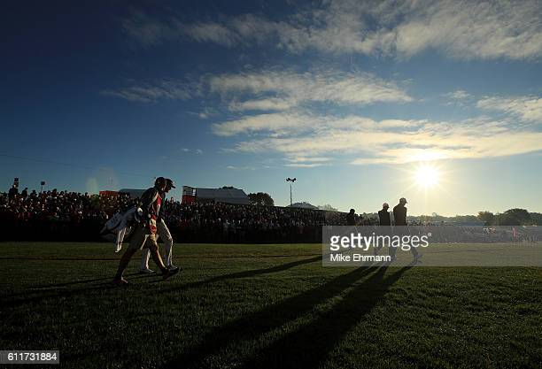 Jimmy Walker of the United States walks off the first tee with Justin Rose and Chris Wood of Europe during morning foursome matches of the 2016 Ryder...