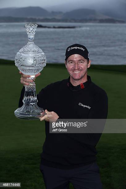 Jimmy Walker poses with the trophy after winning the ATT Pebble Beach National ProAm at the Pebble Beach Golf Links on February 9 2014 in Pebble...