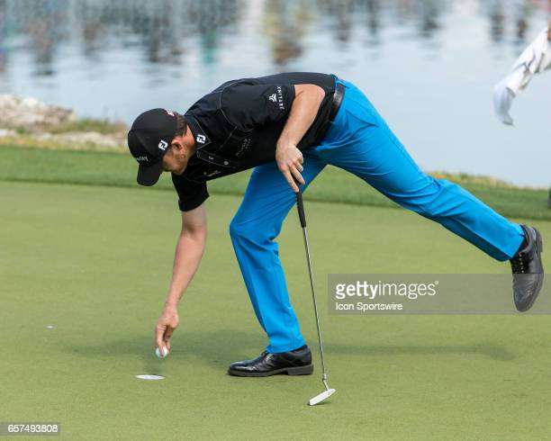 Jimmy Walker retrieves his ball after making a birdie putt and win a hole back against Dustin Johnson during the third round of the WCG-Dell...