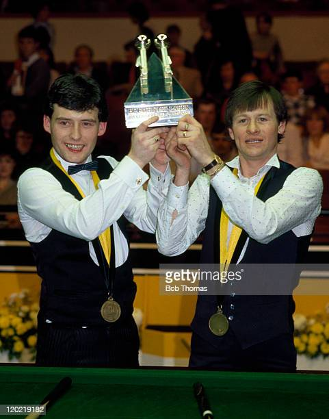 Jimmy White of England and Alex Higgins of Northern Ireland raise aloft the trophy after defeating Willie Thorne and Cliff Thorburn in the World...