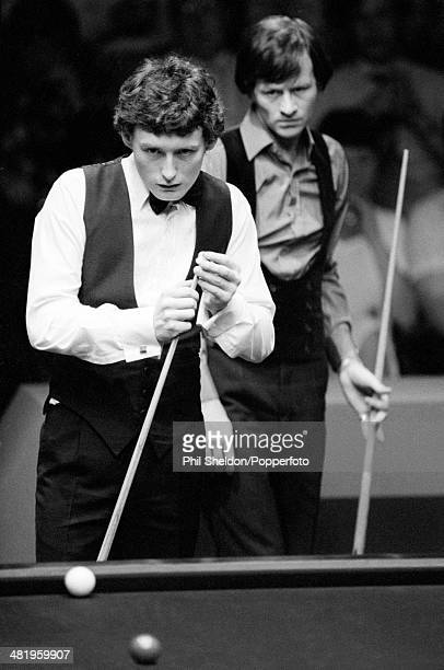 Jimmy White of Great Britain lining up his shot whilst being watched by Alex Higgins of Great Britain during the World Snooker Championship semifinal...