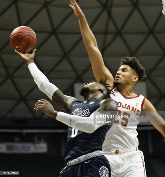 Jimond Ivey of the Akron Zips shoots the ball as he is defended by Bennie Boatwright of the USC Trojans during the first half of their game at the...