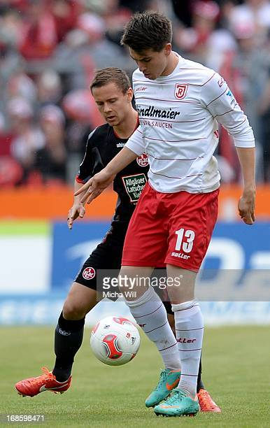 JimPatrick Mueller of Regensburg is challenged by Chris Loewe of Kaiserslautern during the second Bundesliga match at Jahnstadion on May 12 2013 in...