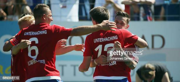 JimPatrick Mueller of Unterhaching celebrates with team mates after scoring his team's first goal during the third league playoff leg one match at...