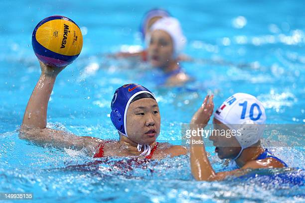Jin He of China looks to move the ball against Giulia Rambaldi of Italy during the Women's Water Polo semifinal match at the Water Polo Arena on...