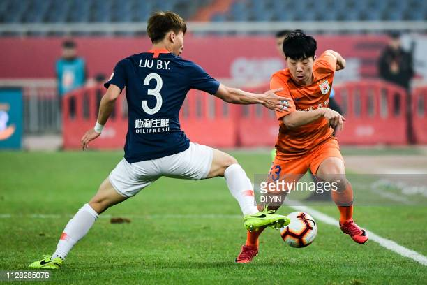 Jin jingdao of Shandong Luneng gets away from challenge from Liu Boyang of Beijing Renhe during the 2019 Chinese Super League match between Shandong...