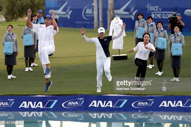Jin Young Ko of Korea her caddie David Brooker and her agent Soo jin Choi leap into Poppie's Pond next to the 18th green after her win during of the...