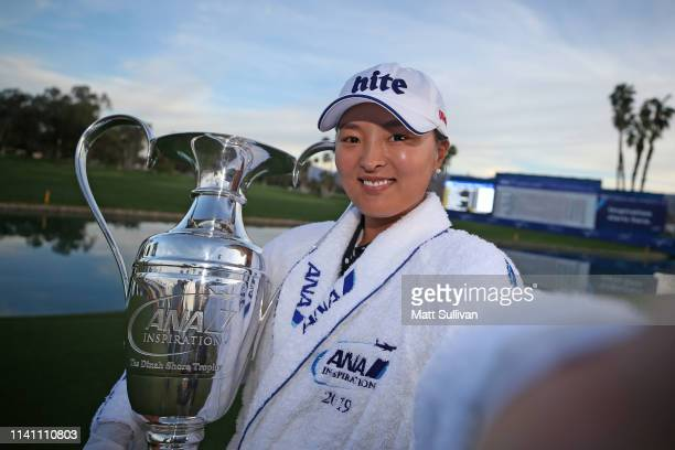 Jin Young Ko of South Korea imitates a selfie with the Dinah Shore Trophy after winning the ANA Inspiration on the Dinah Shore course at Mission...