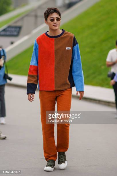 Jin Ze wears sunglasses, a brown, red and blue striped pullover, orange pants, outside Kenzo, during Paris Fashion Week - Menswear Spring/Summer...